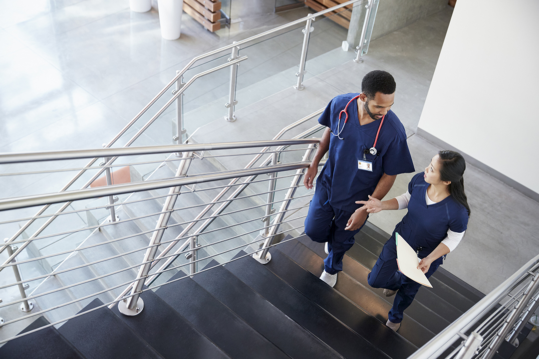 Two healthcare colleagues talking on the stairs at hospital
